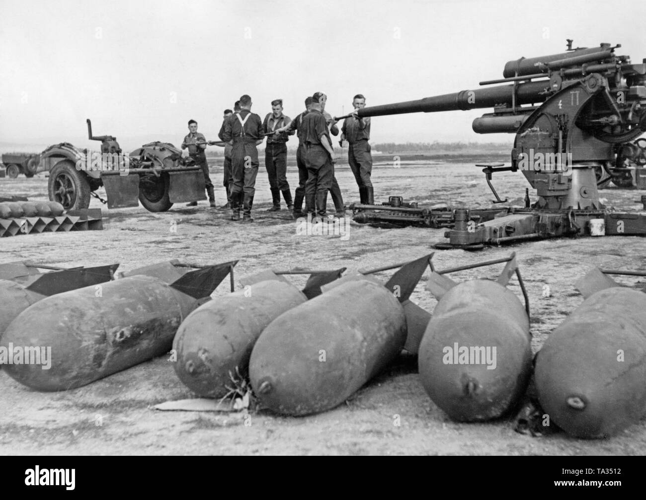Photo of a group of soldiers of the Flak corps 88 of the Condor Legion cleaning a 8.8cm Flak 18/36/37 on an airfield in Spain, 1939. The soldiers are cleaning the cannon barrel. In front of it, there are 250kg aerial bombs. - Stock Image