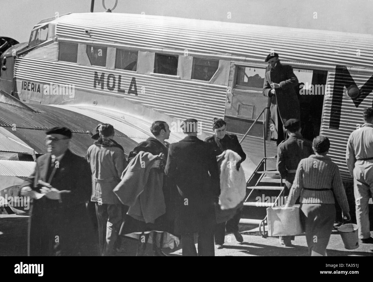 Photo of a German Junkers Ju 52 of the Spanish airline Iberia 1939 at the airport of Salamanca, Castile and Leon, Spain, through the windows of the new terminal. Soldiers and civilians are getting off the aircraft. The machine is named 'Mola', after general Emilio Mola Vidal (died 1937), one of the leaders of the uprising of General Francisco Franco. During the Civil War, the Deutsche Lufthansa and the Iberia (founded in 1927) carried out scheduled flights mostly with German pilots in the Spanish national zone from 1937. The aircraft were provided by the Deutsche Lufthansa AG. - Stock Image