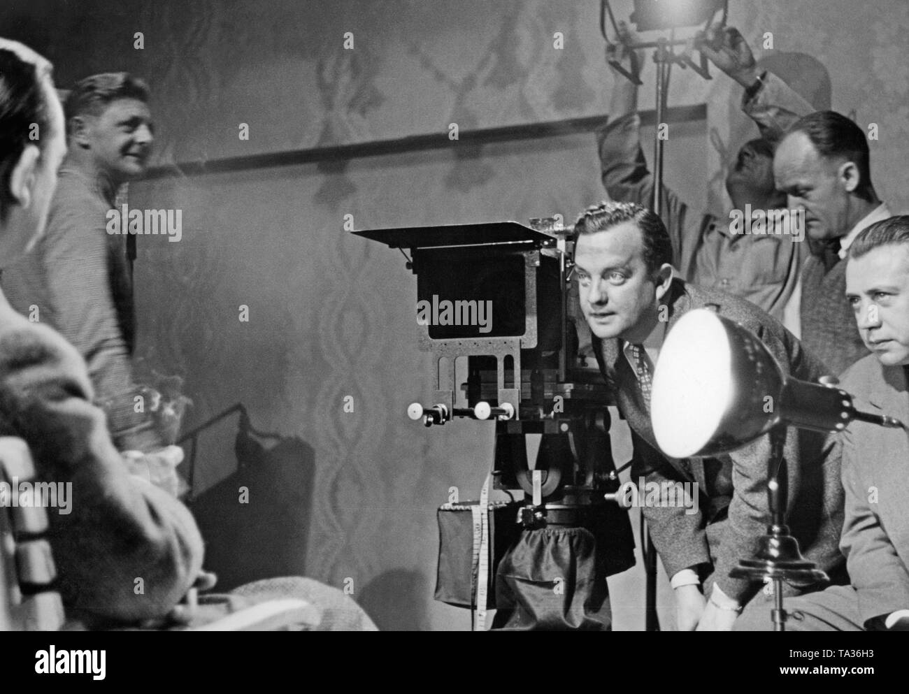 This photo shows cameraman Friedl Behn-Grund (next to the camera), who is looking at the face of actor Curt Goetz to find the right light for him. - Stock Image