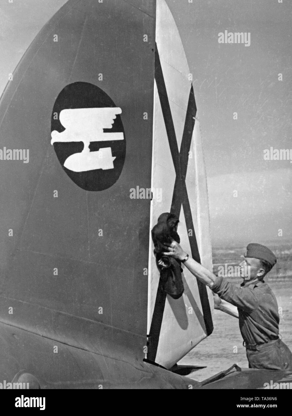 Photo of a legionary from the ground personnel of the Fliegertruppe (air force) of the Condor Legion, who is cleaning a vertical stabilizer of the fighter bomber Heinkel He 111 on an airfield in Spain, 1939. The aircraft belongs to the battle group 88. (Hull cockade: eagle performing nosedive with bomb). On display the Saint Andrew's Cross, the tail cockade of the Spanish air force. - Stock Image