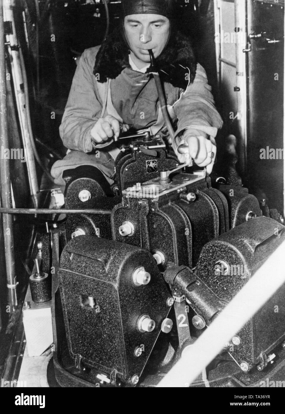 Photo of a camera-man operating a giant aerial camera. Here, the aerial camera was used to make a new map of California. Due to the innovative ten-lens system, an area of ??2000 sq. kms could be shot from the highest possible altitude. The cameraman must use an oxygen device for an easy breathing due to the height reaching up to the stratosphere. - Stock Image