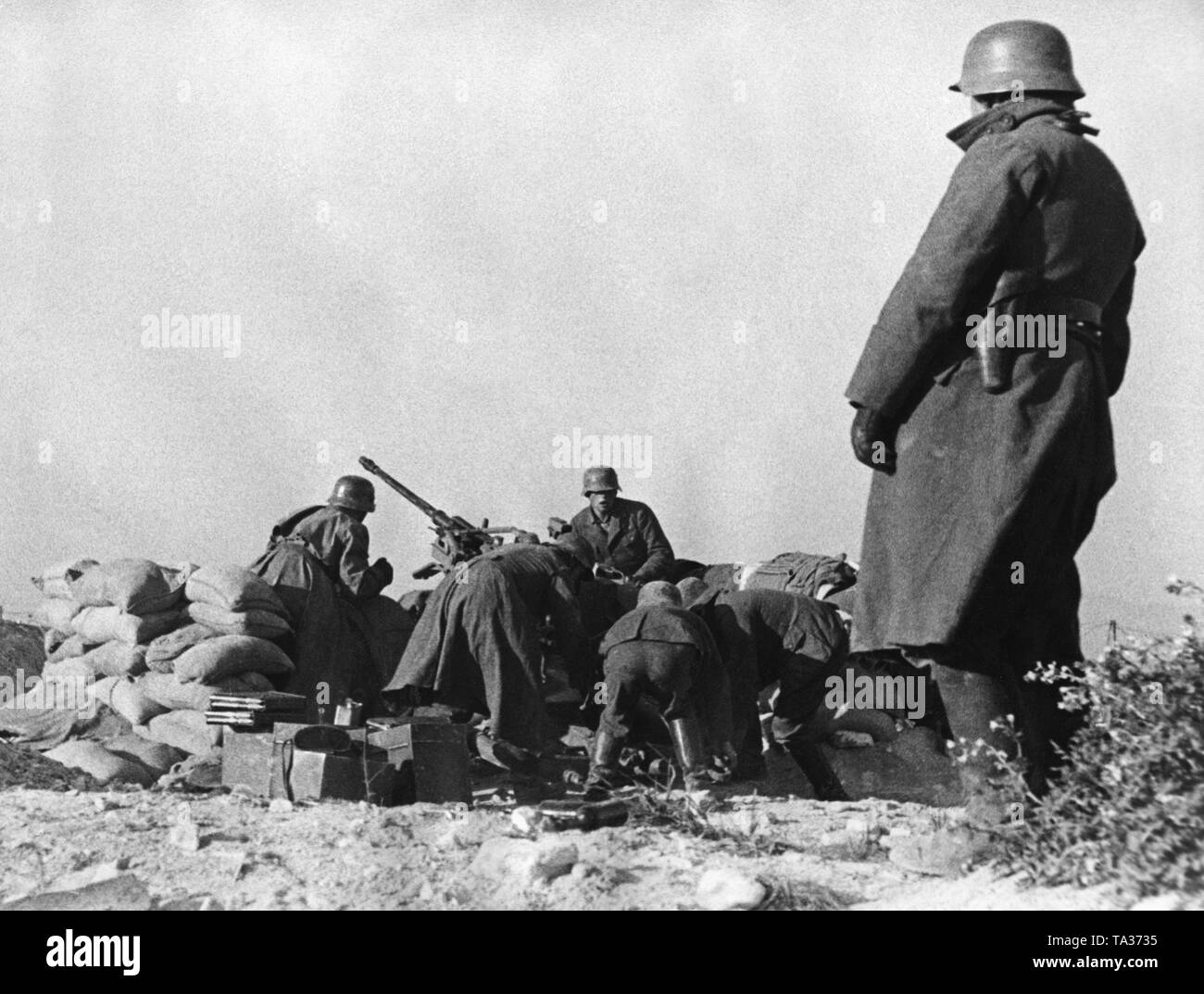 Undated photo of an anti-aircraft unit of the Condor Legion in a ground attack. The soldiers use a 2cm Flak 30 for the operation. The position is protected by sandbags. In the foreground, a standing officer. The soldiers are wearing M35 steel helmets. - Stock Image