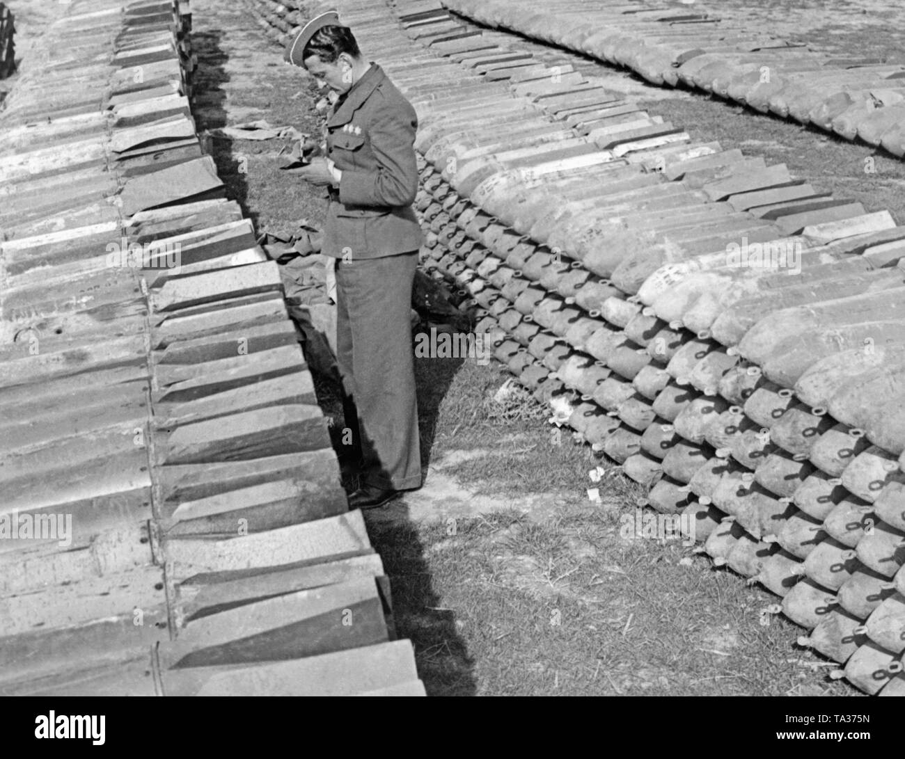 A first lieutenant of the Condor Legion inspects the bomb stock of 250kg aerial bombs piled up on an airfield in Spain. - Stock Image