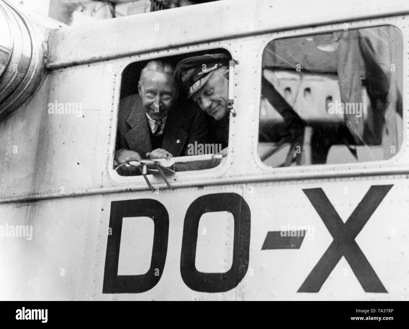 Crown Prince Wilhelm (left) looks out the window of a Donier DO-X together with the captain. - Stock Image