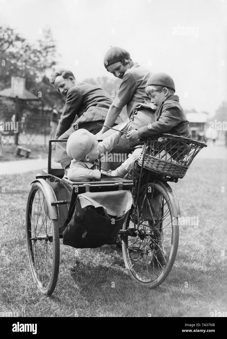 A family with two children is riding a tandem with sidecar through a park. The parents look at their two playing children. The older boy holds a can and a stick in his hand, while the younger child reaches for it. - Stock Image