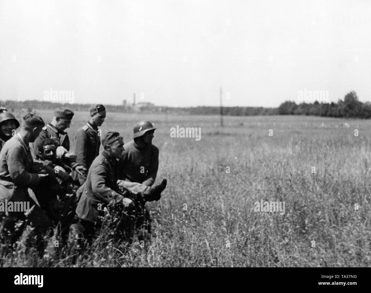 German soldiers are trying to drag a wounded man from the front lines to a dressing station. Stock Photo