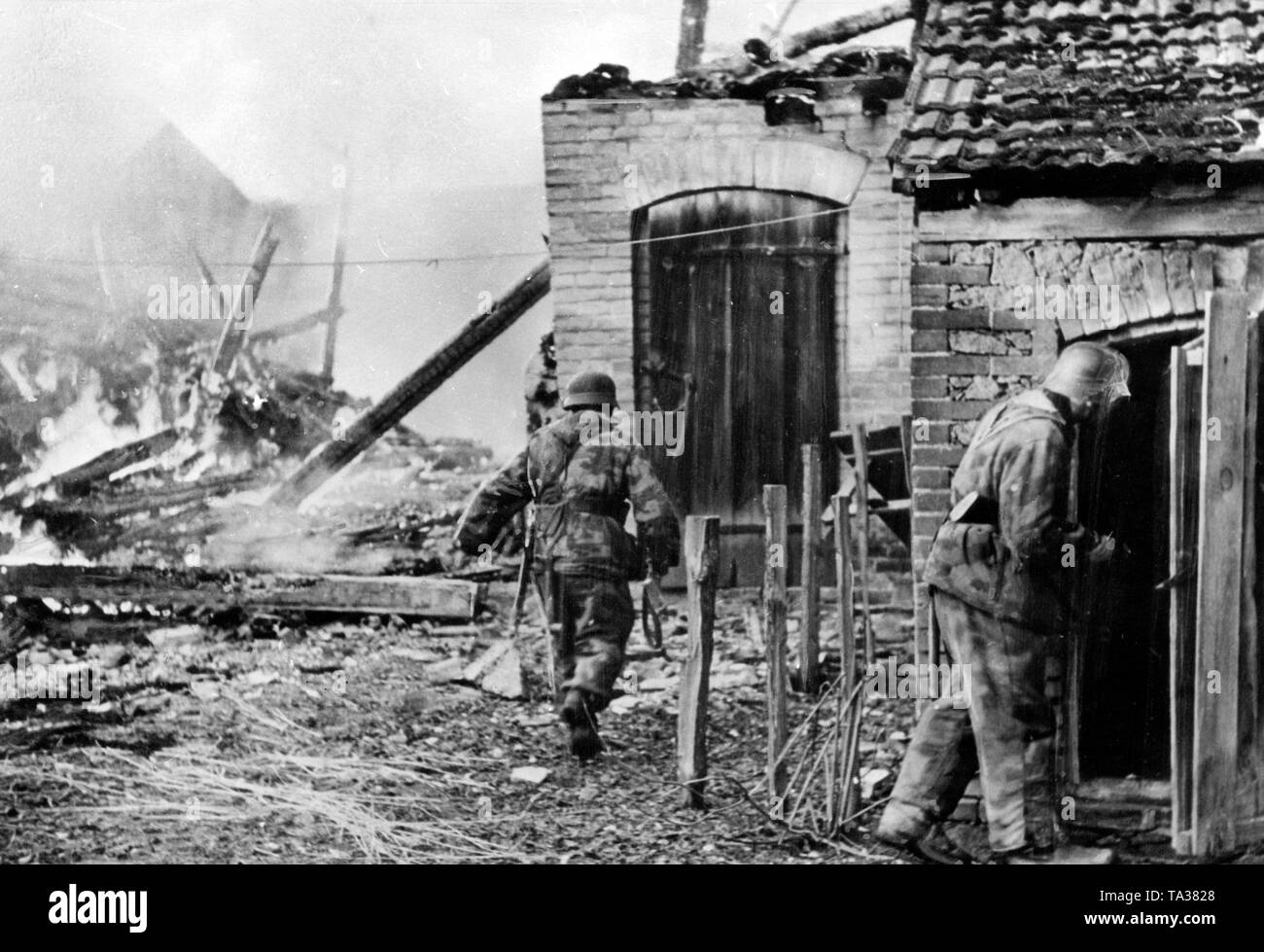 Marines of the Armed Forces search houses in a reconquered village for remaining Red Army soldiers. Stock Photo