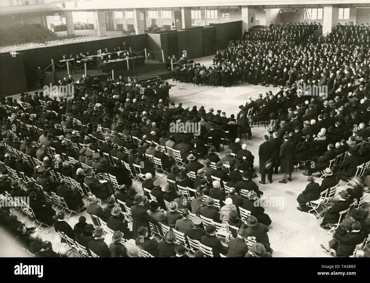 Meeting of creditors of the Bank fuer Deutsche Beamtes. At this point the money of the depositors is already gone. The meeting takes place in a car hall at the Kaiserdamm. - Stock Image