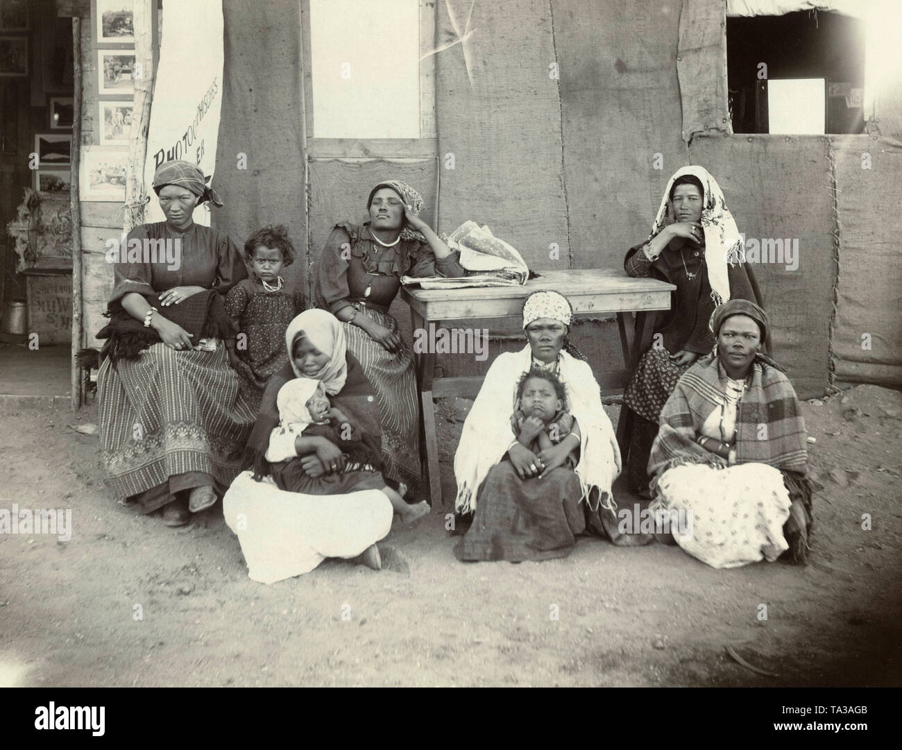Six women with three children in European clothes in front of a photographer's studio in German Southwest Africa. - Stock Image