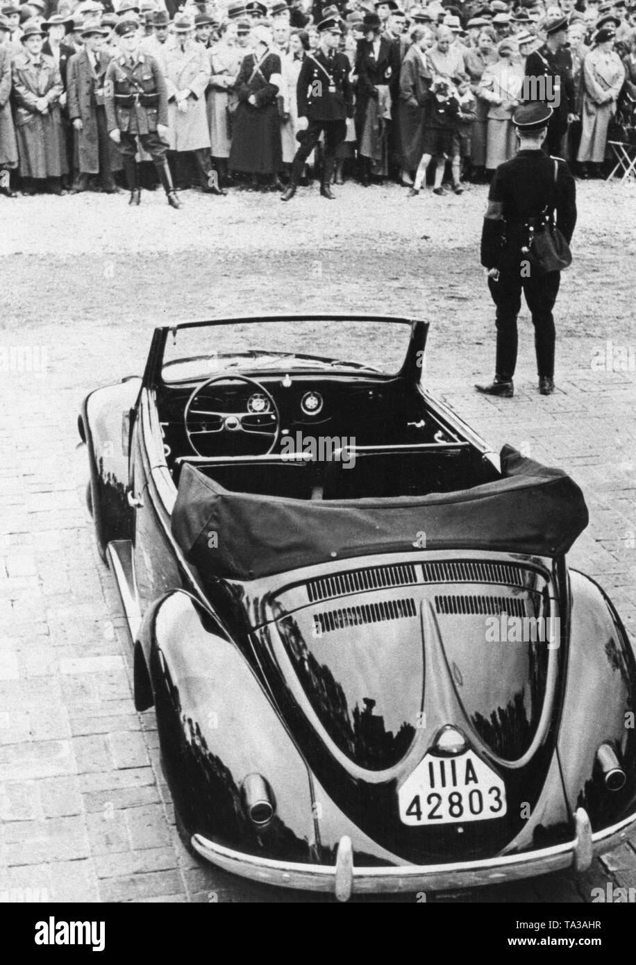 An SS man guards a Beetle convertible at his presentation during a propaganda event in Berlin. - Stock Image