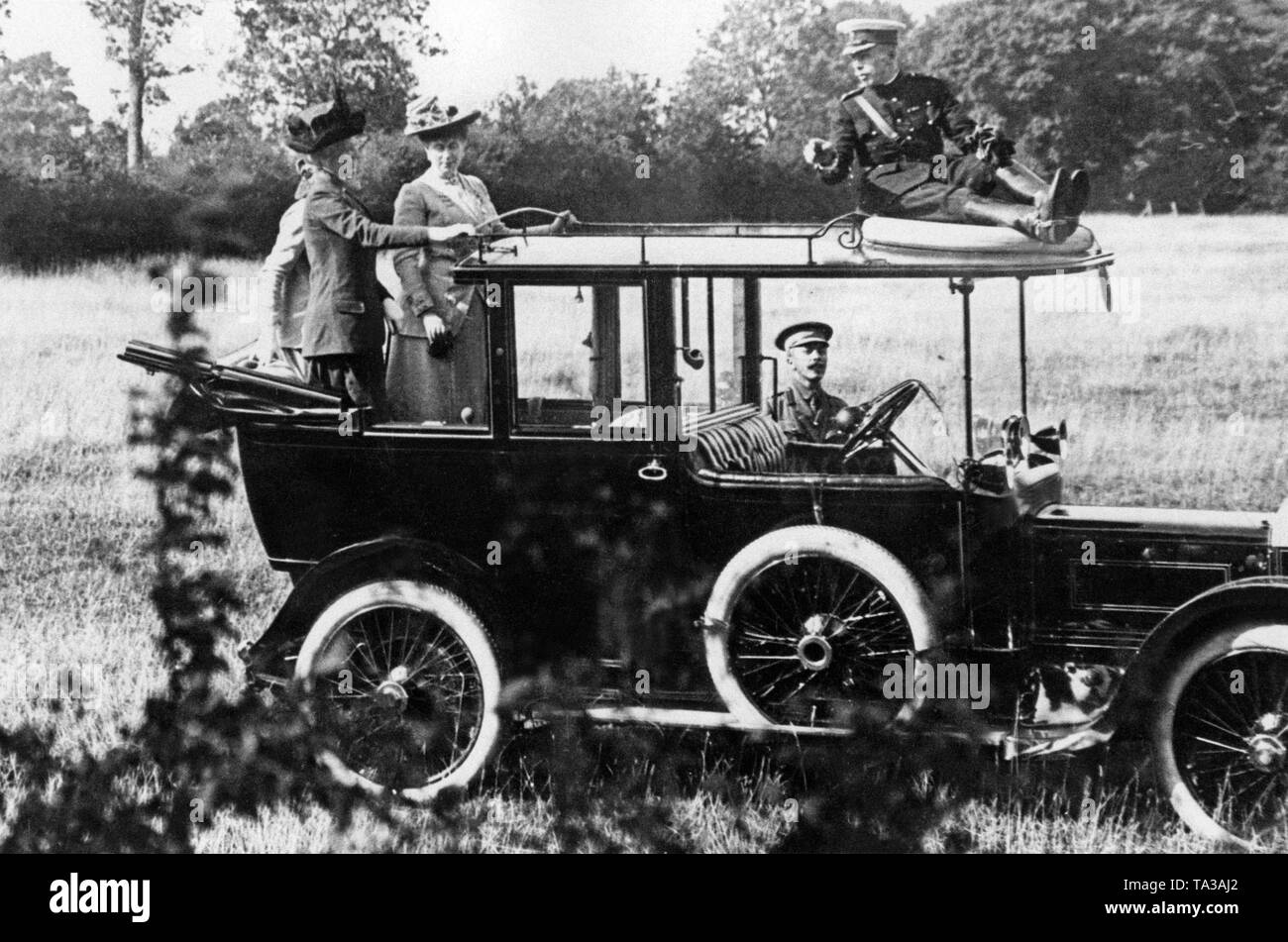 Queen Mary (standing, 3rd from the left), the wife of the English King George V, on a Rolls Royce. Stock Photo
