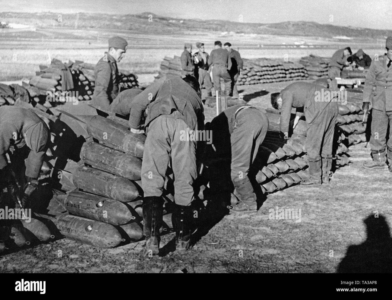 Photo of soldiers of the Condor Legion on an airfield in Spain, who are preparing the bombs. There are further bomb stacks in the background. - Stock Image