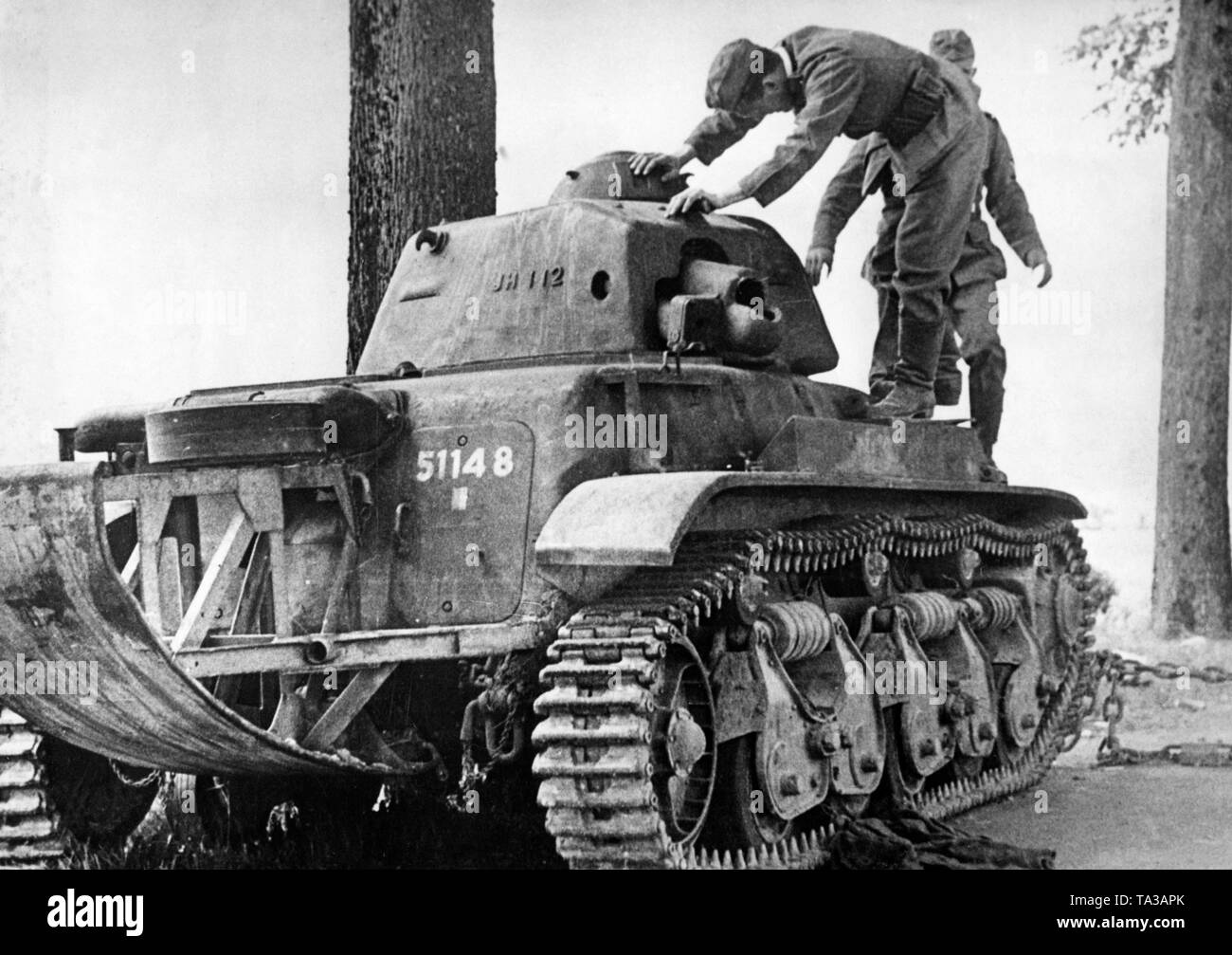 """German soldiers examine a abandoned French tank of the type """"Renault R35"""". Stock Photo"""