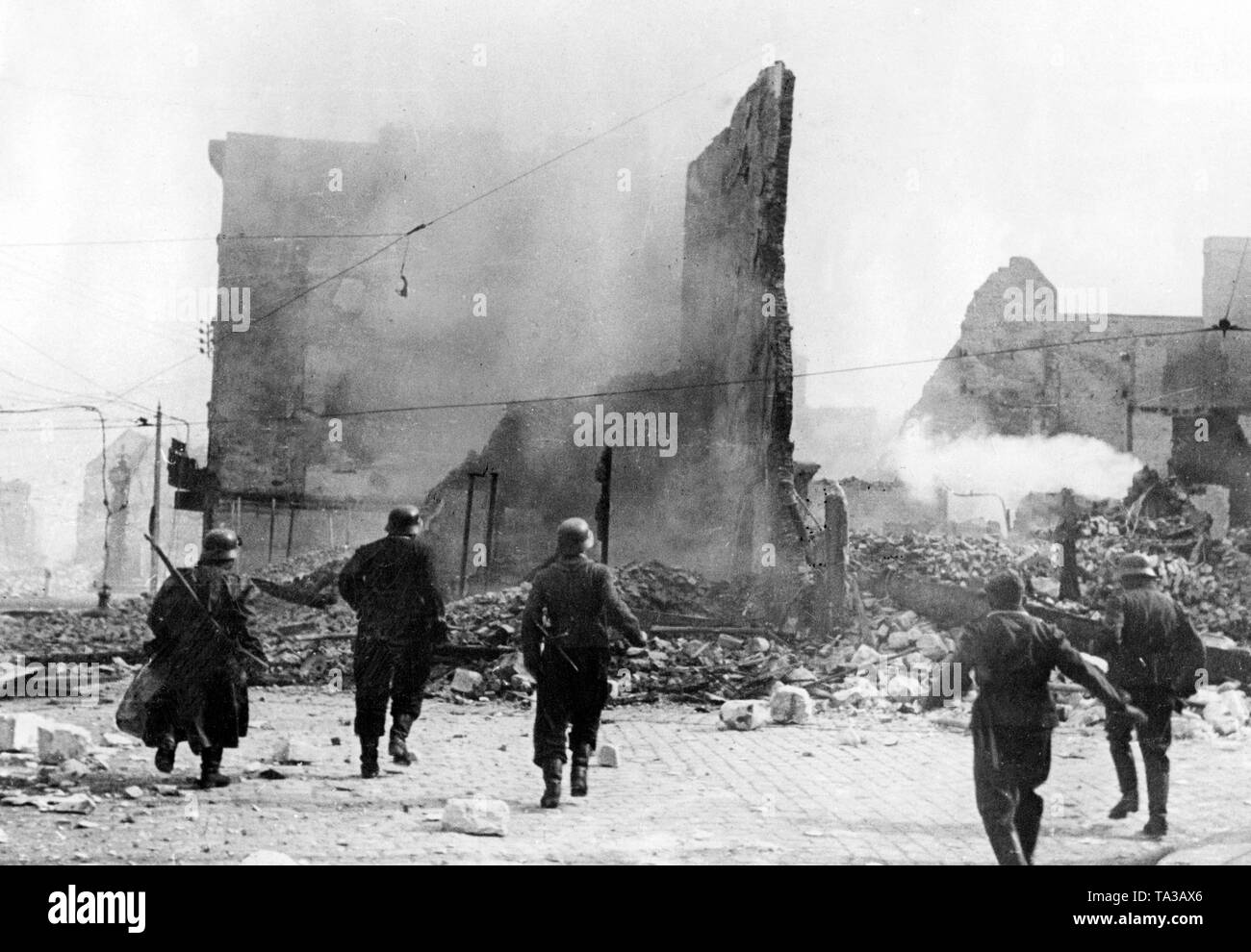A group of German soldiers approach a smoking building, possibly after an air attack. Since only one of the soldiers is carrying a gun, the proximity to the front seems unlikely. Stock Photo