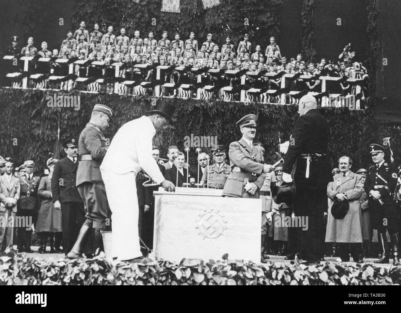 Laying the foundation stone of the Volkswagen plant in the 'Stadt des KdF-Wagens' (City of the KdF Car), now Wolfsburg. Hitler receives the foundation stone hammer from the bricklayer foreman. - Stock Image