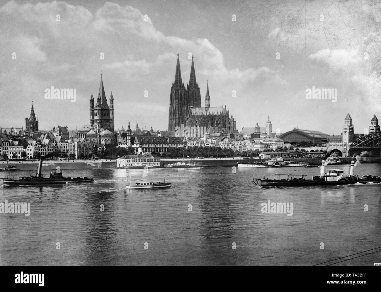 View of the Cologne Rhine riverbank in front of the Great St. Martin Church from 1928. Several large and small steamboats operate on the Rhine. There are people on the shore. The towers, left to right: Town Hall, Great St. Martin Church, Cologne Cathedral. Right in the picture, the Hohenzollern Bridge. Left beside, the Station Hall. - Stock Image