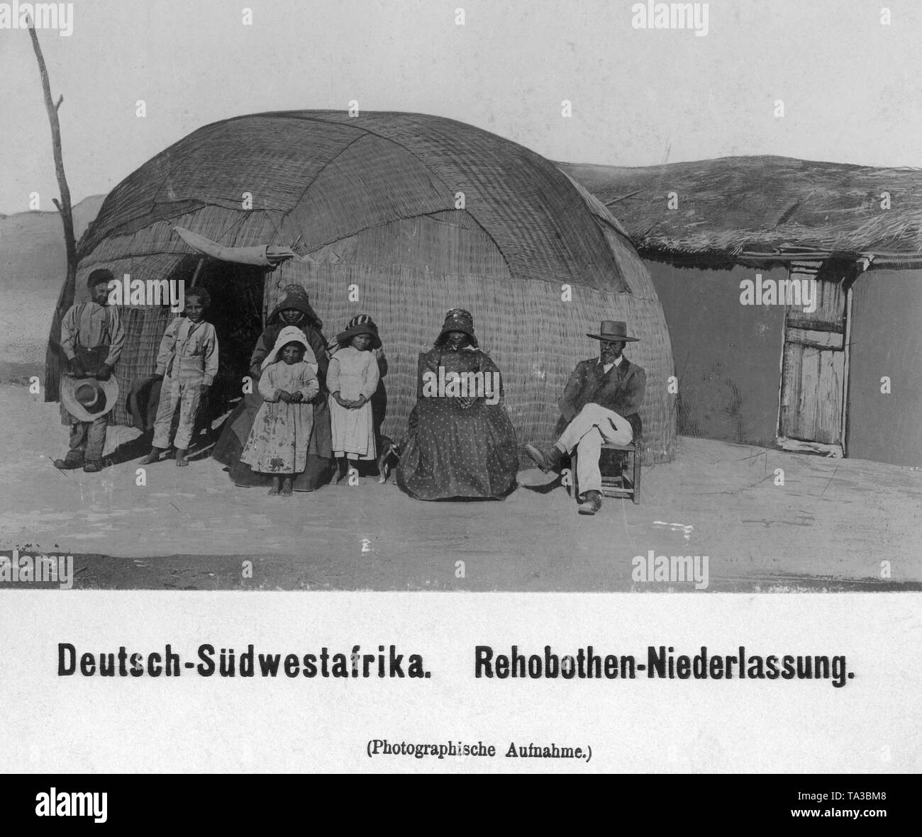 Group of Rehobothers in European clothes in front of a pondok in German Southwest Africa (undated shot). Stock Photo