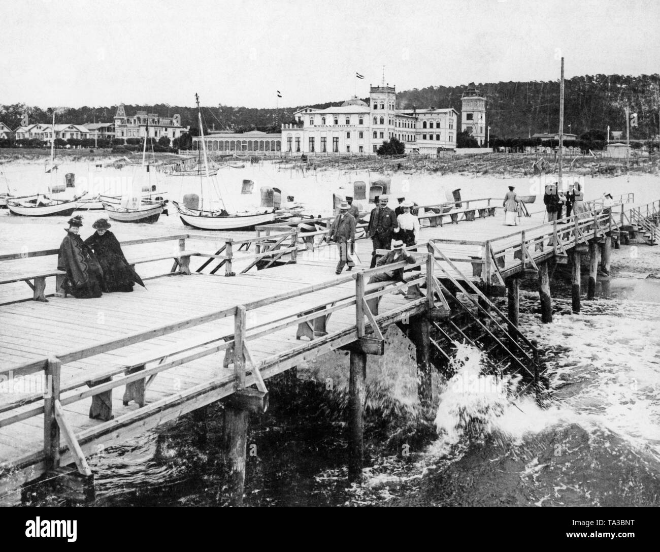 Holidaymakers on the pier in front of the seaside resort of Miedzyzdroje in Pomerania, on the beach are small sailing boats. - Stock Image