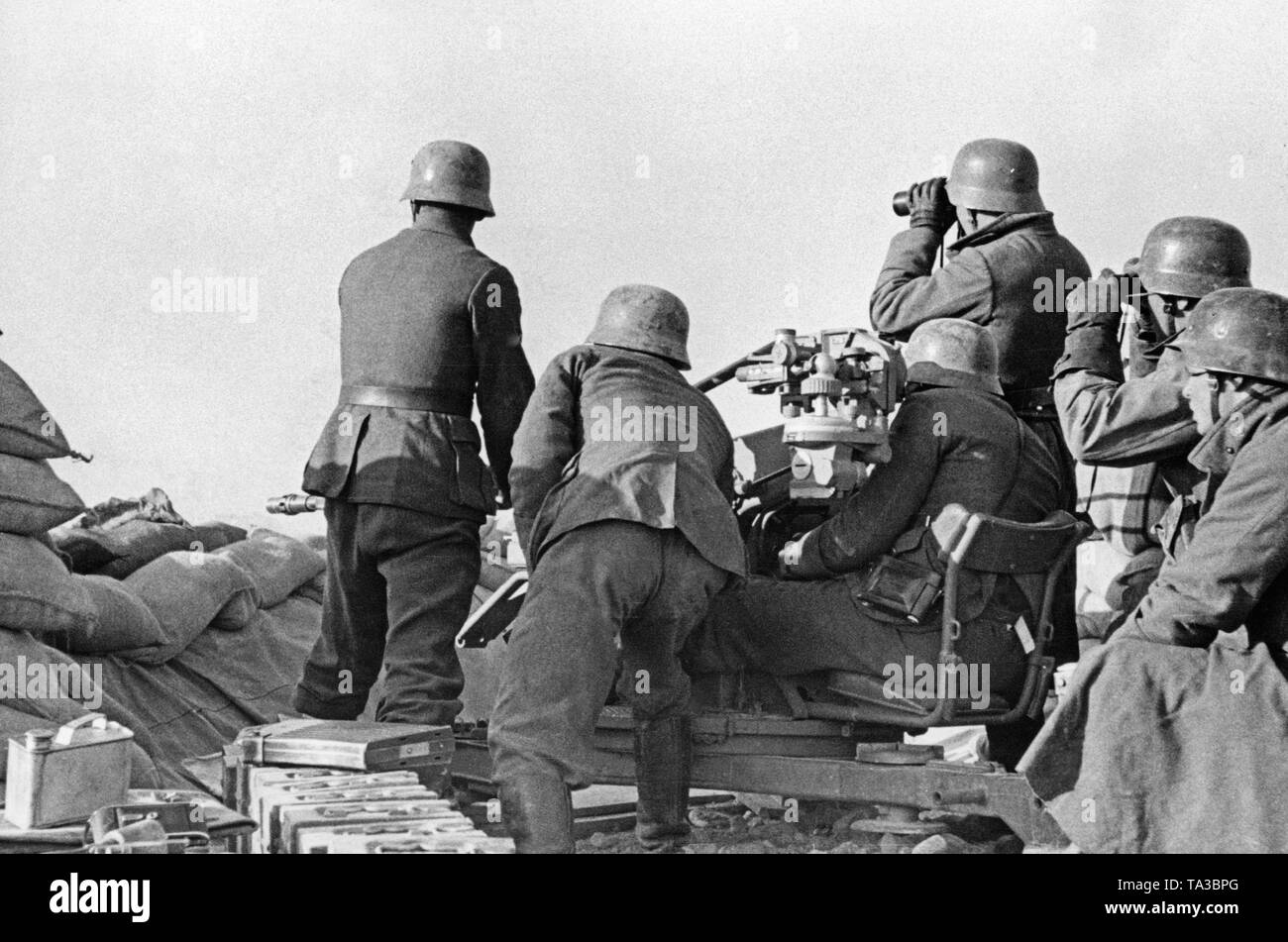Undated photo of an anti-aircraft unit of the Condor Legion during a deployment in the Spanish Civil War. Two men are aiming at ground target using a 2cm FLAK 39 in a sandbag position. An officer (left) picks the targets. On the left in the front there are crates of ammunition. The soldiers are wearing M35 steel helmets. - Stock Image