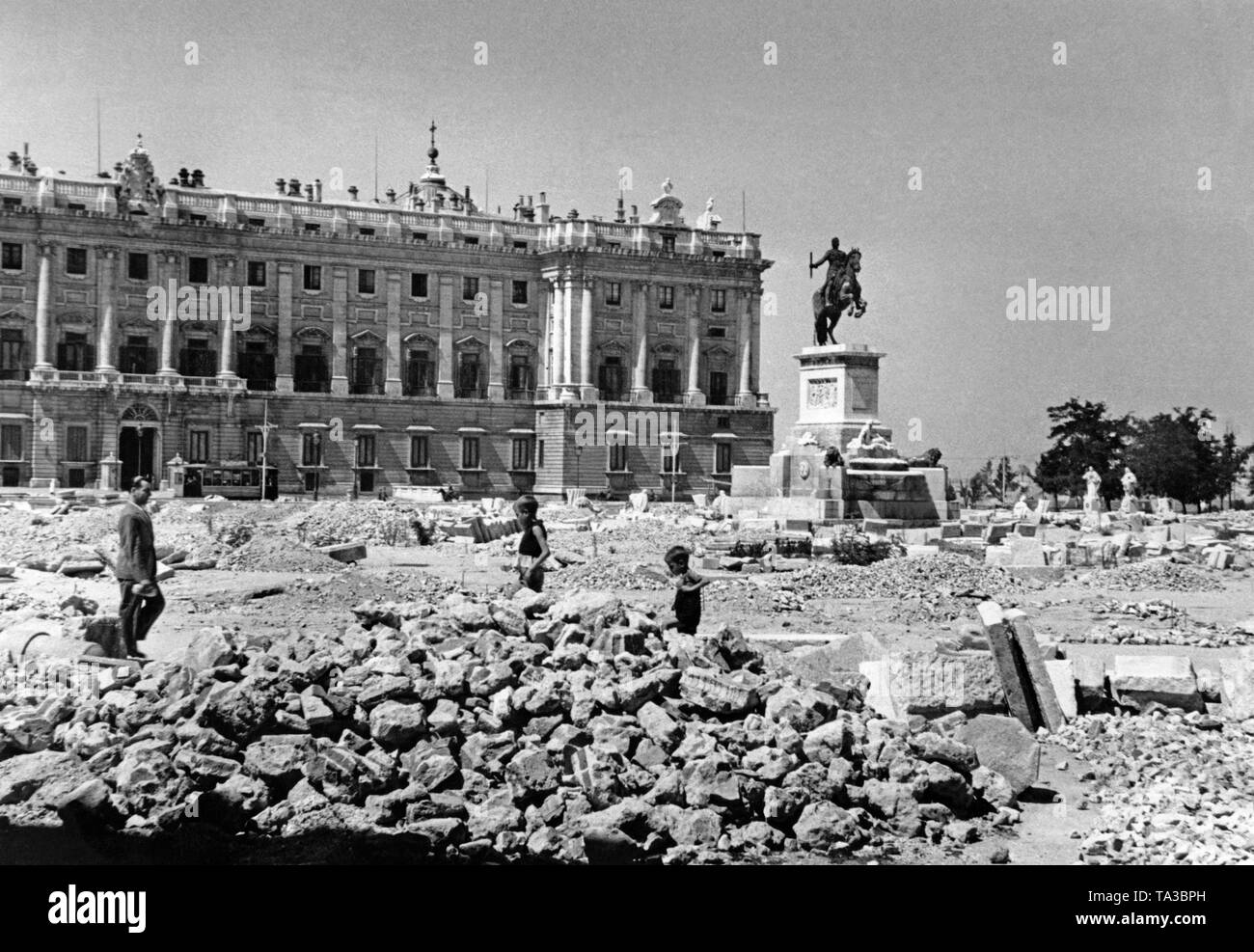 Photo of the Plaza del Oriente in Madrid after the invasion of the Spanish troops under General Francisco Franco in ther spring of 1939. In the background, the Spanish Royal Palace (Palacio Real). In front of it, the equestrian statue of King Philip IV (Felipe IV, 1605-1665). The pavement of the square is torn open for barricade construction. Children are playing. - Stock Image