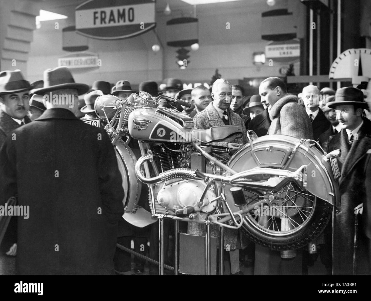 Crown Prince Wilhelm (in the middle behind the motorcycle) probably at a motor show in Berlin. He is looking at a motorcycle of the brand Ardie. - Stock Image