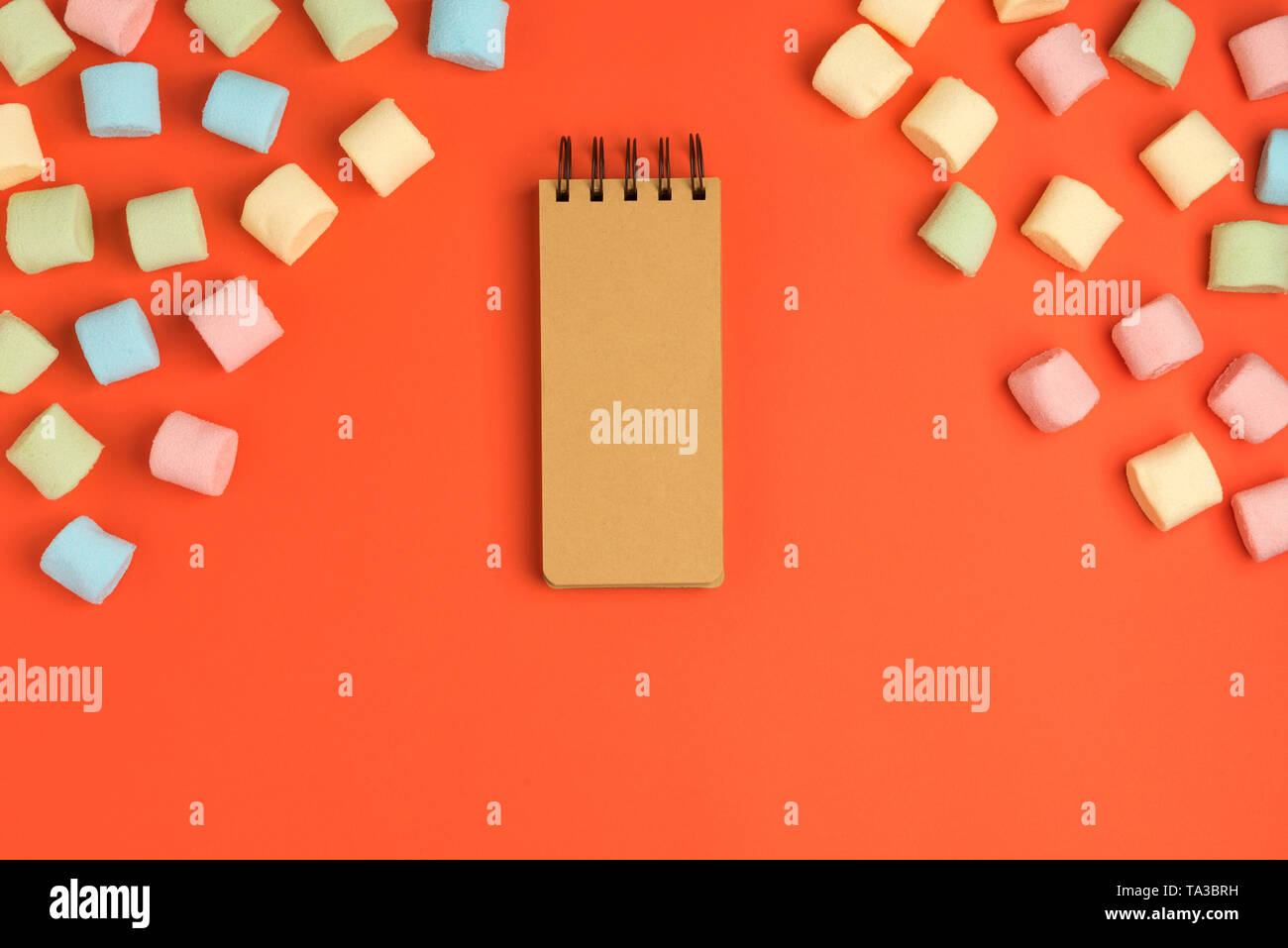 Coral paper background with marshmallow and notepad. Place for your text. Cozy sweet background - Stock Image