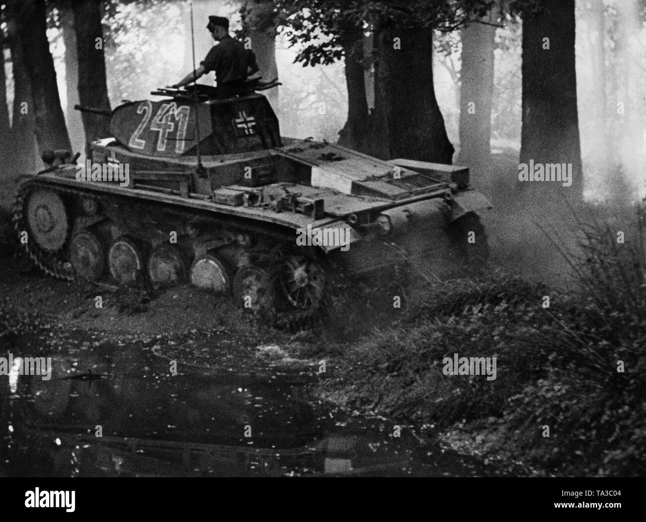 A German Panzer II advances through a forest. Probably a moviestill from Sieg im Westen (Victory in the West). Stock Photo