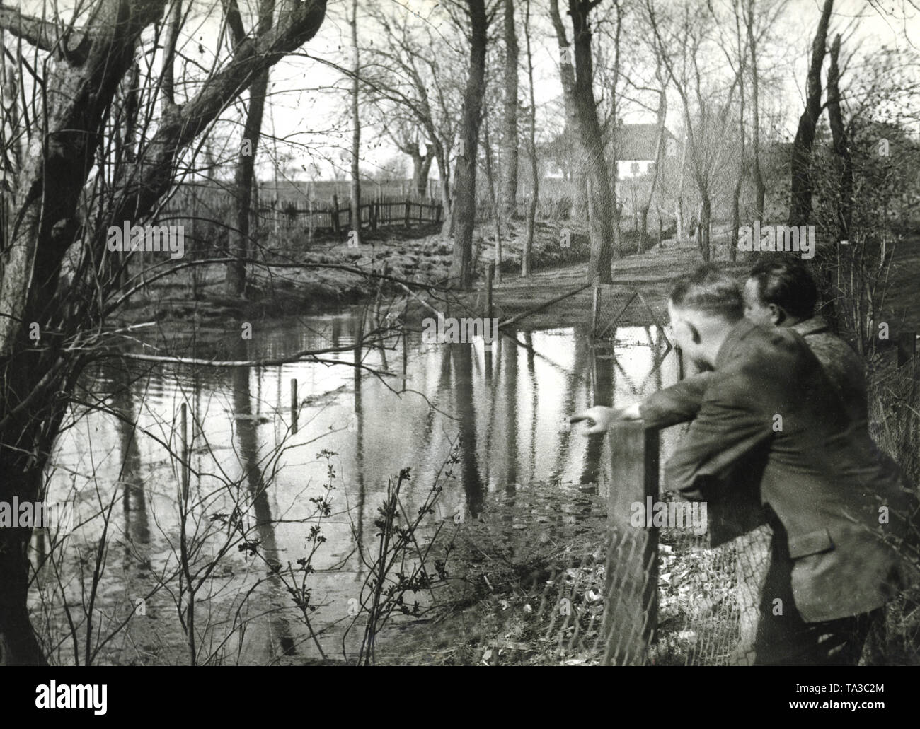 This pond of a farmyard is divided in the middle by the border between the newly-created Poland and Danzig. In fact, several sticks stuck into the pond symbolize the strange bordering (Undated photo). Stock Photo