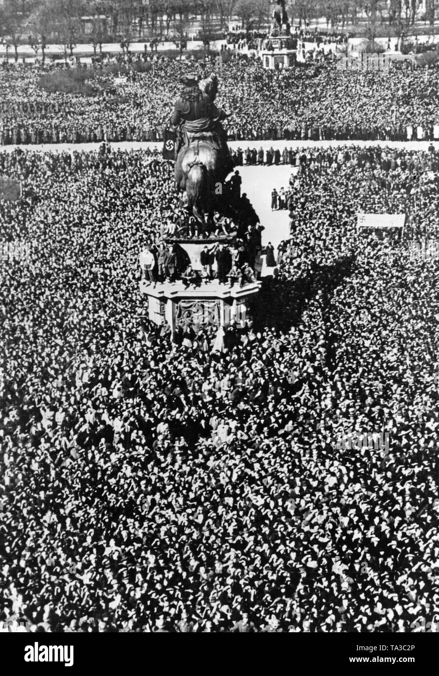 People gather in front of the Prinz Eugen monument on the Heldenplatz in Vienna. Nazi leader Adolf Hitler announces the annexation of Austria to the German Reich on the Heldenplatz. - Stock Image