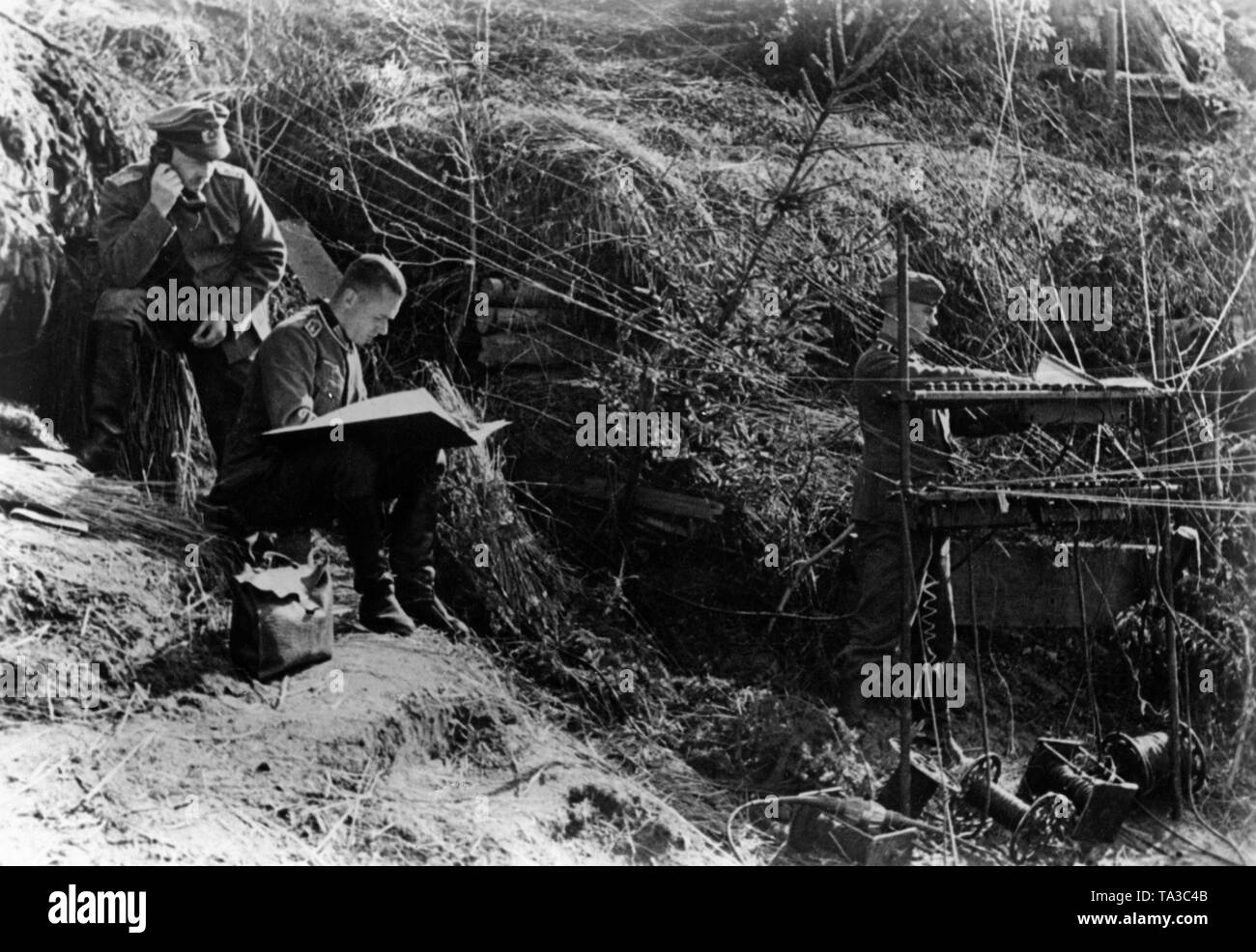 Command post of the Wehrmacht during Operation Typhoon in early October 1941. The goal of this operation was the conquest of Moscow. The picture shows radio wires connecting the general staff to the front. Left in the picture two officers. Photo: war reporter Sepp Jaeger. Stock Photo