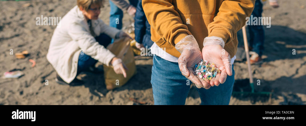 Hands with microplastics on the beach - Stock Image