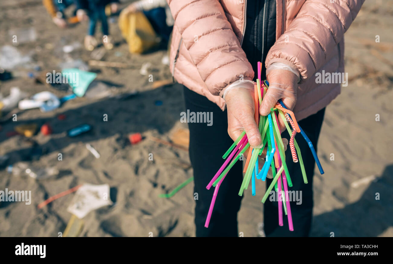Woman showing handful of straws collected on the beach - Stock Image