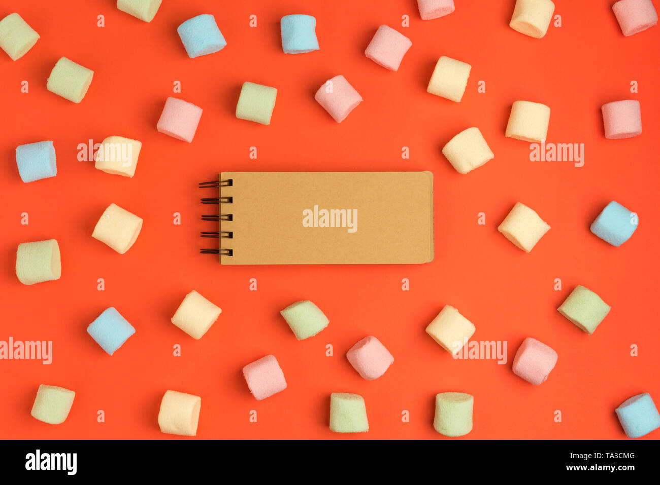 Coral paper background with marshmallow and blank notepad. Place for your text. Cozy sweet background - Stock Image