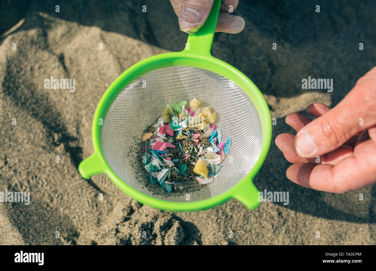 Colander with microplastics on the beach - Stock Image