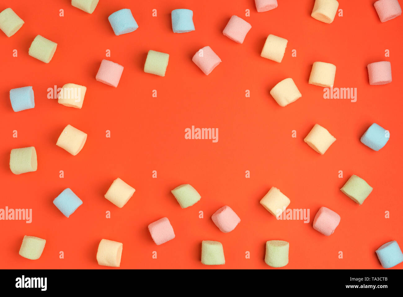 Living coral, color of the year 2019. Mini marshmallows on trendy pastel coral background. Flat lay, copy space - Stock Image