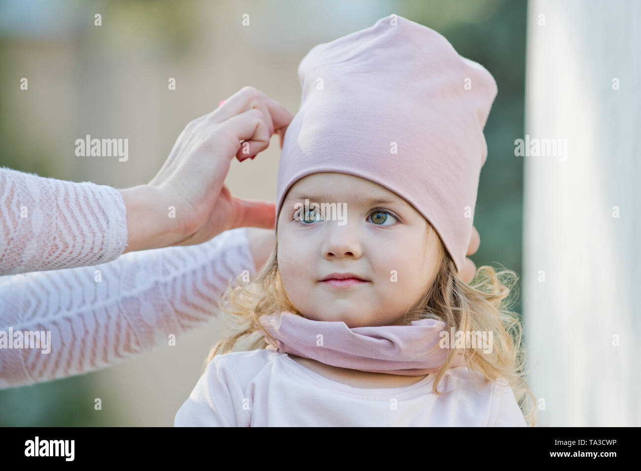 d00ad1b9 Girl get hat put on head by female hands Stock Photo: 247167698 - Alamy