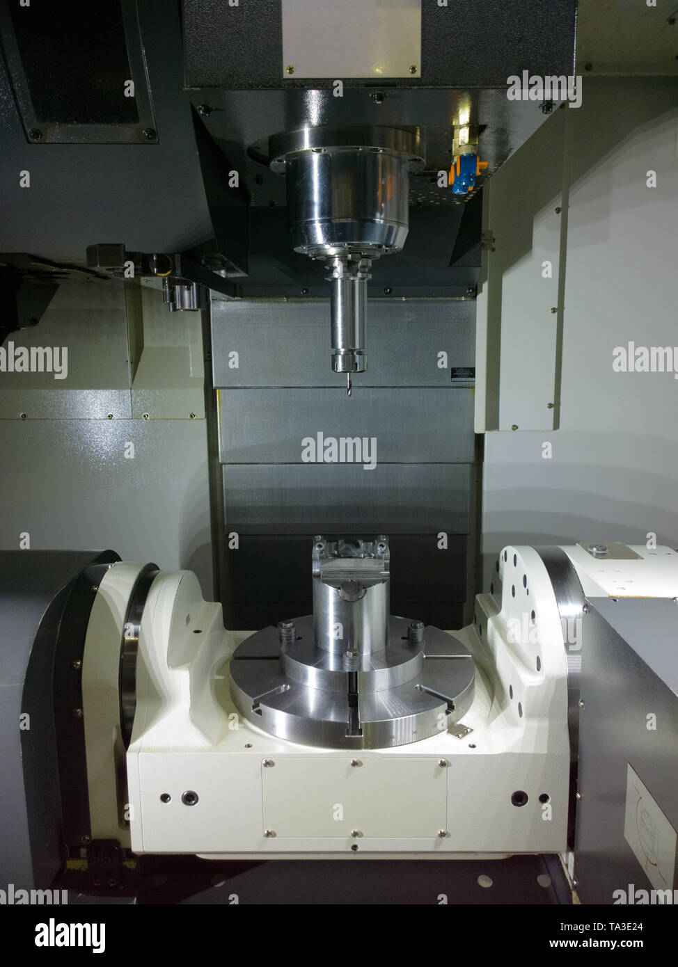 The five-axis Computer Numerical Control CNC machine waiting for stock change. - Stock Image