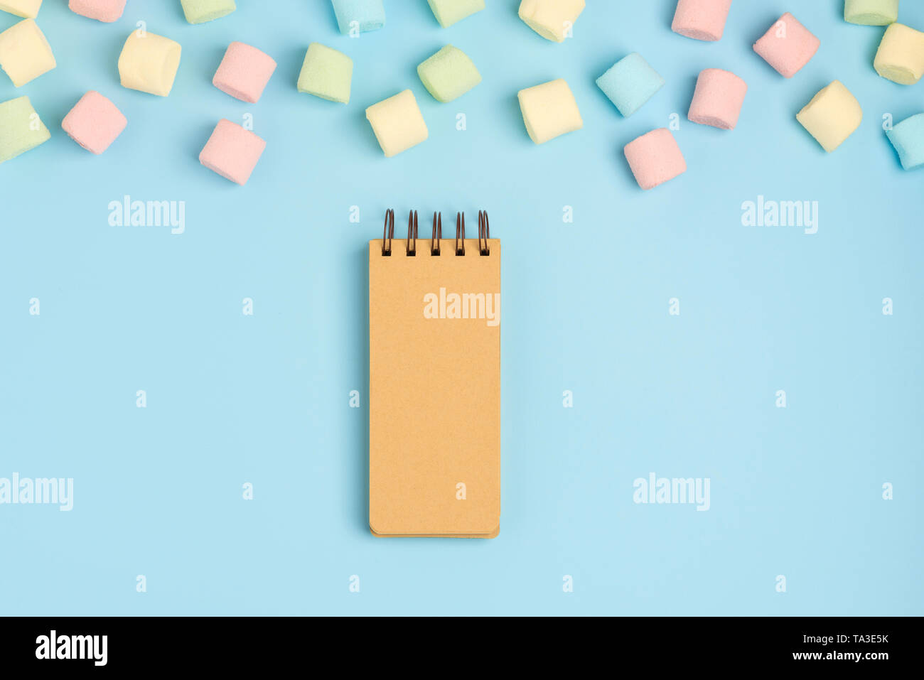 Blue paper background with marshmallow and notepad. Place for your text. Cozy sweet background - Stock Image