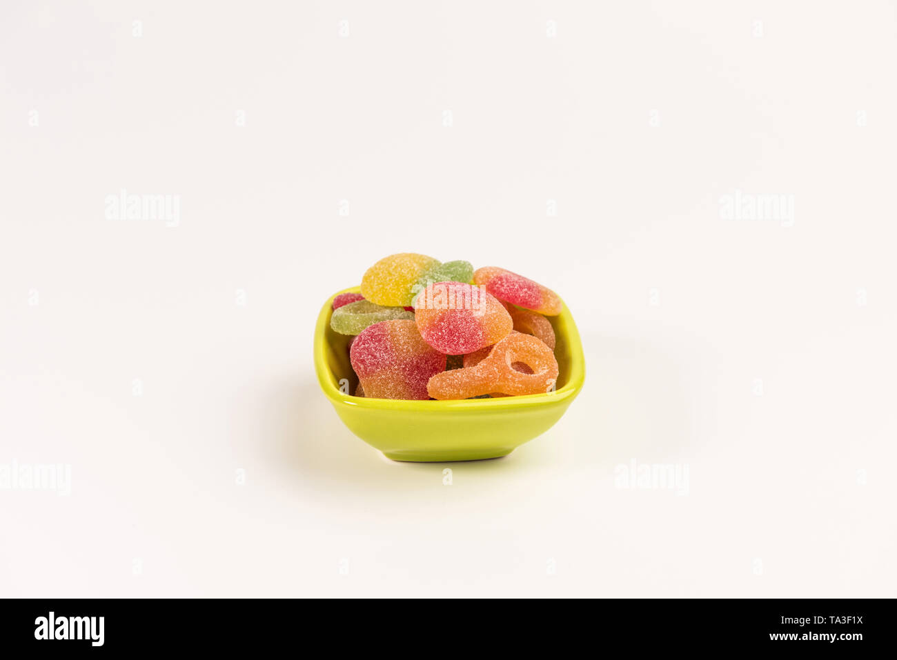 Small bowl with gummy candies isolated on white background. - Stock Image
