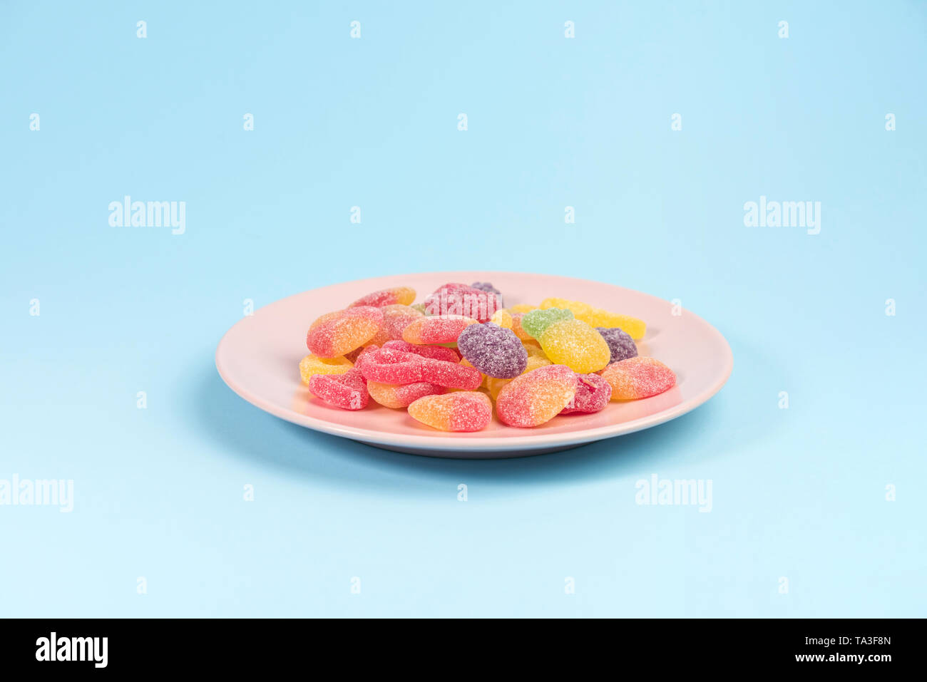 Pink plate with gummy candies on blue background. - Stock Image