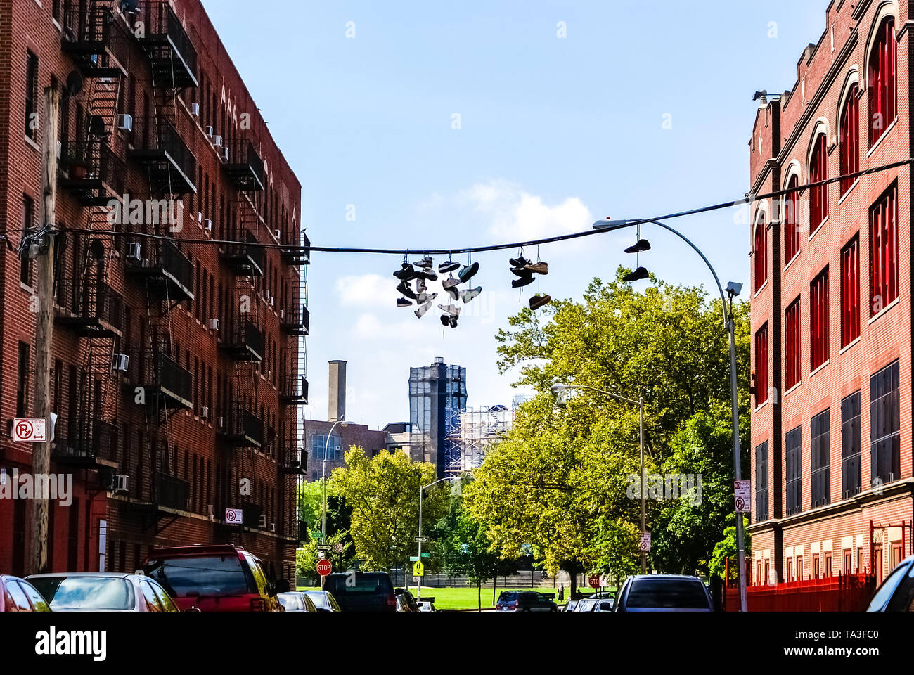 New York, USA - August 15, 2008: Pairs of sneakers hanging by street gangs from power lines on the streets of an American city. - Stock Image