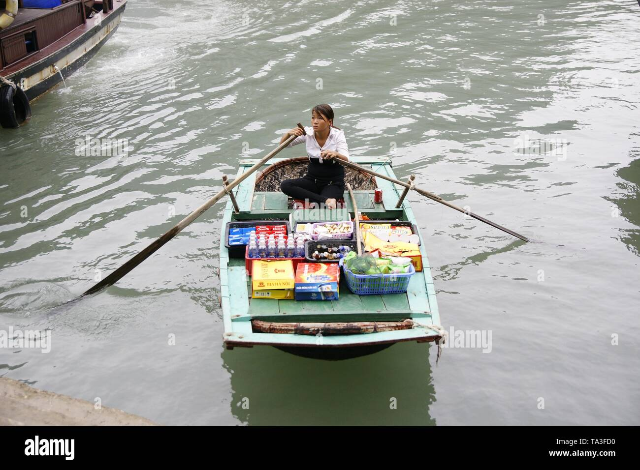 Ha long, vietnam - October 31, 2011: Food vendor in a boat offering food to tourists sailing on the sea bay of China in Vietnam. Stock Photo