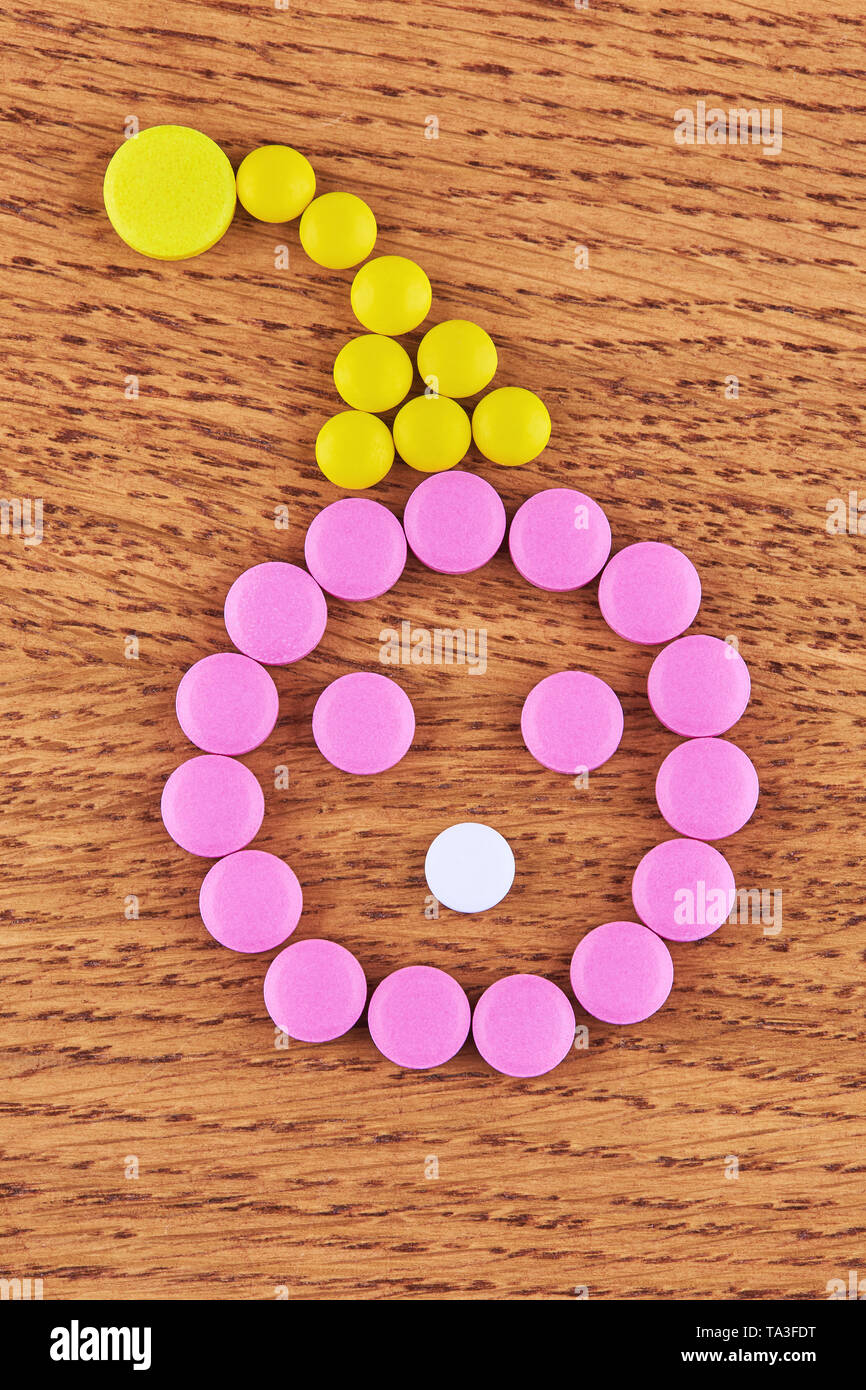 Face made of pink and white pills in yellow hat on wooden background. - Stock Image