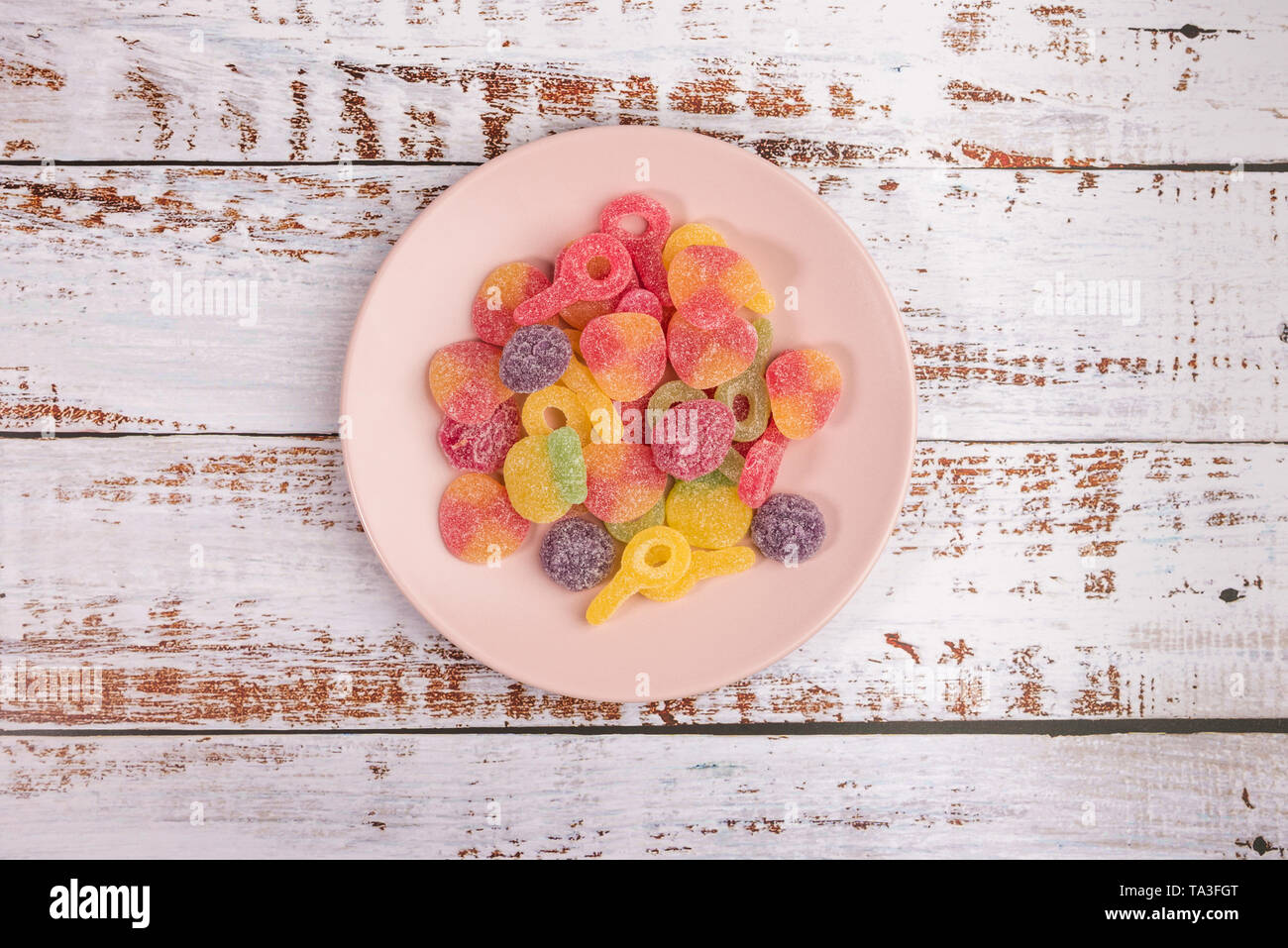 Pink plate with gummy candies on white wooden background. Top view. - Stock Image