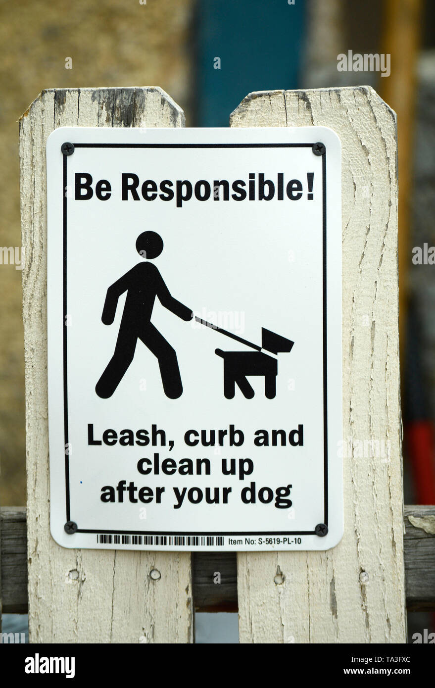 A sign on a picket fence asks pet owners to leash their dogs and clean up after their dogs. - Stock Image