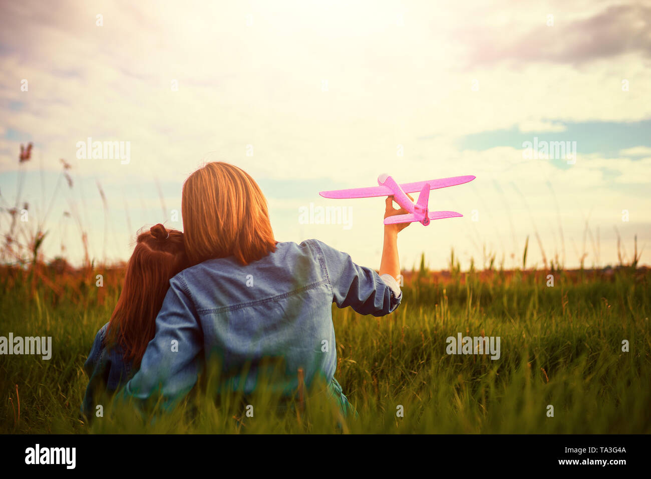 Back view of woman and girl in denim outfits hugging and playing with pink toy plane while sitting on green grass against cloudy sky together - Stock Image