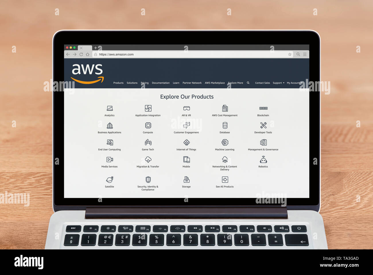 An Apple Macbook displays the Amazon Web Services (AWS) website (Editorial use only). - Stock Image