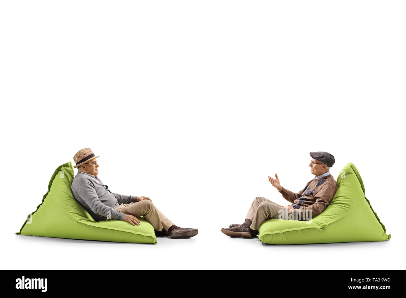 Full length profile shot of two senior men sitting on bean bags and having a conversation isolated on white background - Stock Image