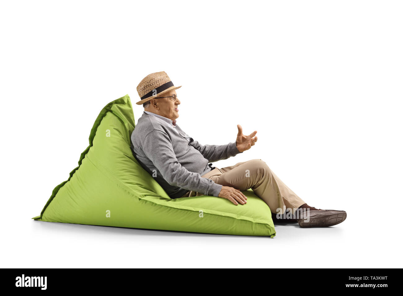 Full length shot of a senior man sitting on a bean-bag and gesturing with hand isolated on white background - Stock Image