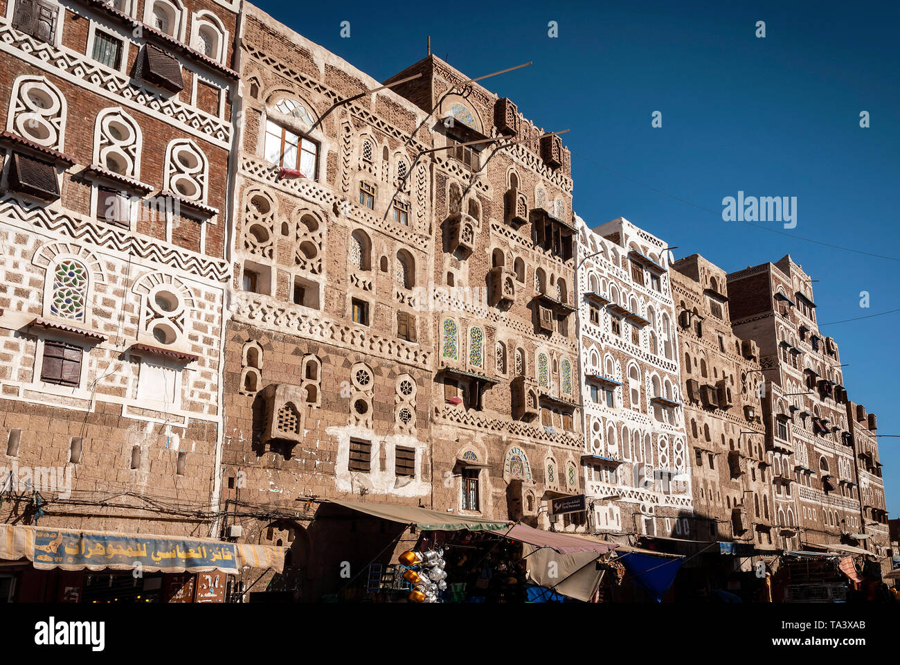 street scene and local heritage architecture buildings in old town of sanaa yemen - Stock Image